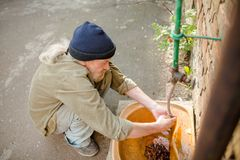 Side view of homeless man washing hands in old sink in the street. Tramp taking care og hands hygiene Stock Photography