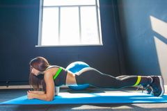 Side view image of fit sportive woman doing plank core exercise training back and press muscles on mat in gym wearing. Sportswear stock photo