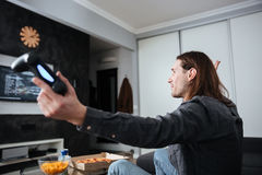 Side view image of young sad man gamer sitting at home. Indoors and play games with joystick Stock Image