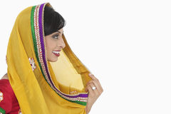 Side view of Indian female holding dupatta over white background Royalty Free Stock Photo
