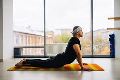 Side view of indian man doing the cobra pose in a bright fitness studio royalty free stock photography
