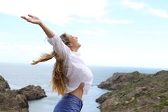Side view of a joyful girl raising arms to the wind Royalty Free Stock Photography