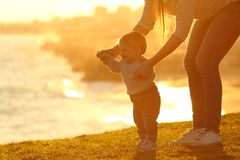Kid learning to walk and mother helping at sunset. Side view of a kid learning to walk and mother helping him on the grass outdoors at sunset with a city in the Royalty Free Stock Image