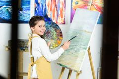 Side view of kid painting and holding palette in workshop of. Art school royalty free stock photo