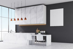 Side view of a kitchen with marble furniture, black walls, panoramic window and a small table with two white chairs. Royalty Free Stock Images