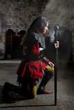 Side View of Knight in Armor With Sword Praying in the Old Church Royalty Free Stock Photography
