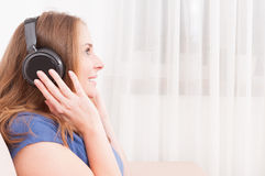 Side view lady on sofa enjoying listening to headphones Royalty Free Stock Photography