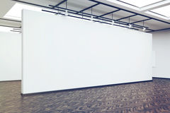 Side view of a large blank wall in an art gallery with dark wood Royalty Free Stock Photo