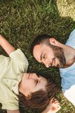 Glad boy and optimistic man during rest. Side view laughing bearded father telling with positive male child during relax. Glad dad and son having leisure royalty free stock images