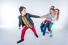 Side view of laughing girls pulling up boy. On grey Royalty Free Stock Image