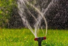 Side view of lawn sprinkler with flow of water fly in an air with copyspace. Side view of lawn sprinkler with flow of water fly in an air, image with copyspace royalty free stock photography