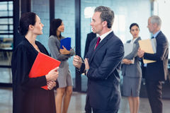 Side view of lawyer interacting with businessman. While standing in office Royalty Free Stock Image