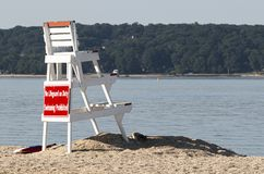 Side view of lifguard standing on the north shore of Long Island looking over the bay. A white lifeguard stand up on the sand looking over the empty water of the stock image