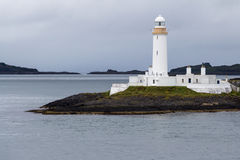 Side view of Lismore lighthouse in Scotland. Side of the white lighthouse of Lismore framed by a gray sea and sky, near Mull and Oban, in the Inner Hebrides of Royalty Free Stock Image