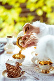 Side view of little beautiful girl`s hands in the scenery of Alice in Wonderland pouring tea into a cup at the table Royalty Free Stock Image
