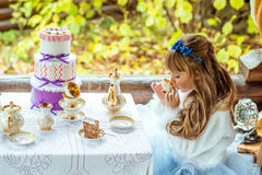 Side view of an little beautiful girl in the scenery of Alice in Wonderland drinking a tea at the table in the park. Side view of an little beautiful girl in the Royalty Free Stock Photo