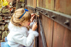 Side view of an little beautiful girl in the scenery of Alice in Wonderland looking into the keyhole of the gate. Side view of an little beautiful girl with long royalty free stock photo