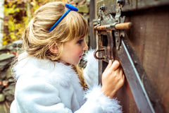 Side view of an little beautiful girl in the scenery of Alice in Wonderland looking into the keyhole of the gate. Side view of an little beautiful girl with long stock images