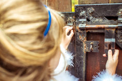 Side view of an little beautiful girl in the scenery of Alice in Wonderland looking into the keyhole of the gate. Side view of an little beautiful girl with long stock photos