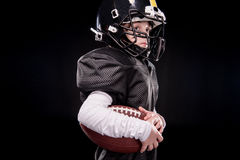 Side view of little boy american football player in uniform holding ball Stock Images