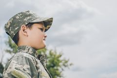 Side view of little boy in camouflage clothing with cloudy sky. On backdrop royalty free stock photography