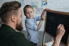 Side view of little boy and father with pieces of chalk drawing picture on blackboard. At home royalty free stock photography
