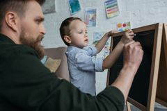 Side view of little boy and father with pieces of chalk drawing picture on blackboard. At home royalty free stock images
