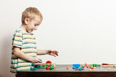 Side view little boy play with toy on table. Spending free time play and education for children. Little boy in striped shirt play with colorful toy on table Royalty Free Stock Photo