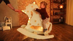 Baby riding rocking toy. Side view of little boy riding white rocking toy in glowing room stock video