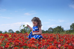 Side view of little brunette girl in dress in bright flowers fie Royalty Free Stock Photography