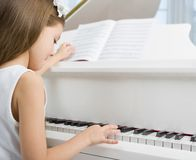 Side view of little child in white dress playing piano Stock Images