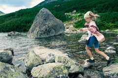 Side view of little girl jumping from stone to stone Royalty Free Stock Photo