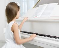 Side view of little girl in white dress playing piano Stock Photo