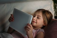 side view of little kid using tablet in bed royalty free stock photo