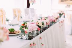 Side view of the little pink flowers in the mini-vases on the wedding table set. stock photo