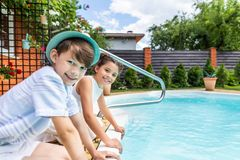 side view of little siblings sitting near swimming pool royalty free stock photography