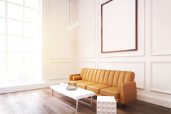 Side view of a living room with poster, brown sofa and a coffee. Side view of a living room interior with white walls, large brown sofa, a coffee table with a Royalty Free Stock Photo