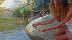 Side View Long Haired Girl Sets Shrimp on Stick on River Bank. Side view pretty long haired girl in white dress sets large grey shrimp on wooden stick on river stock video footage