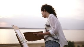 Side view of a lovely woman drawing outdoors on the meadow using an easel and palette. Blurred lake view on the stock footage