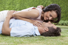 Side view of loving woman lying on man in park Royalty Free Stock Image