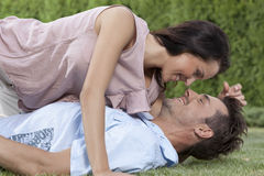 Side view of loving woman lying on man in park Royalty Free Stock Photos