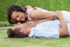 Side view of loving woman lying on man in park Stock Photo