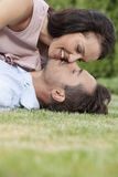 Side view of loving young couple about to kiss in park Stock Image
