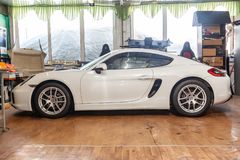 Side view of luxury very expensive new white Porsche Cayman coupe sportcar stands in the detailing box waiting for repair in auto. Novosibirsk, Russia - 08.01.18 royalty free stock photos