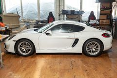Side view of luxury very expensive new white Porsche Cayman coupe sportcar stands in the detailing box waiting for repair in auto. Novosibirsk, Russia - 08.01.18 stock photos
