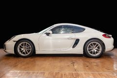 Side view of luxury very expensive new white Porsche Cayman coupe sportcar stands in the detailing box waiting for repair in auto. Novosibirsk, Russia - 08.01.18 stock photography