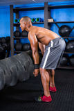 Side view of male athlete picking up tire Royalty Free Stock Photos
