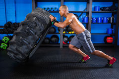 Side view of male athlete pushing tire Royalty Free Stock Photo
