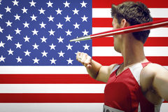Side view of male athlete throwing javelin against American flag Stock Image