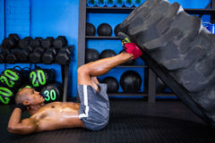 Side view of male athlete with tire in gym Stock Images